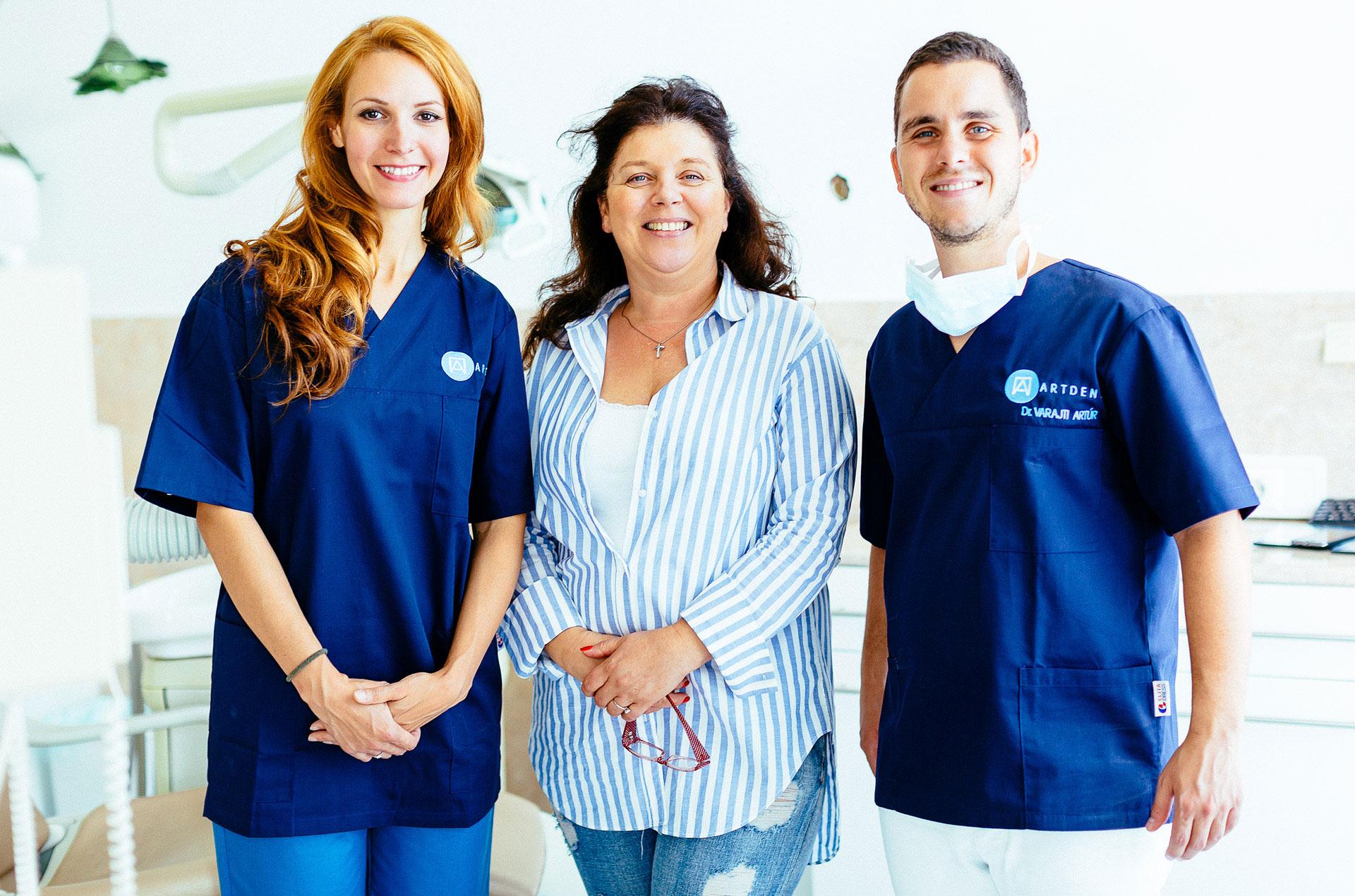 Dr. Varajti Artúr szájsebész, fogorvos áll, mellette a páciens és a fogászati asszisztens a budapesti fogászati rendelőben.
