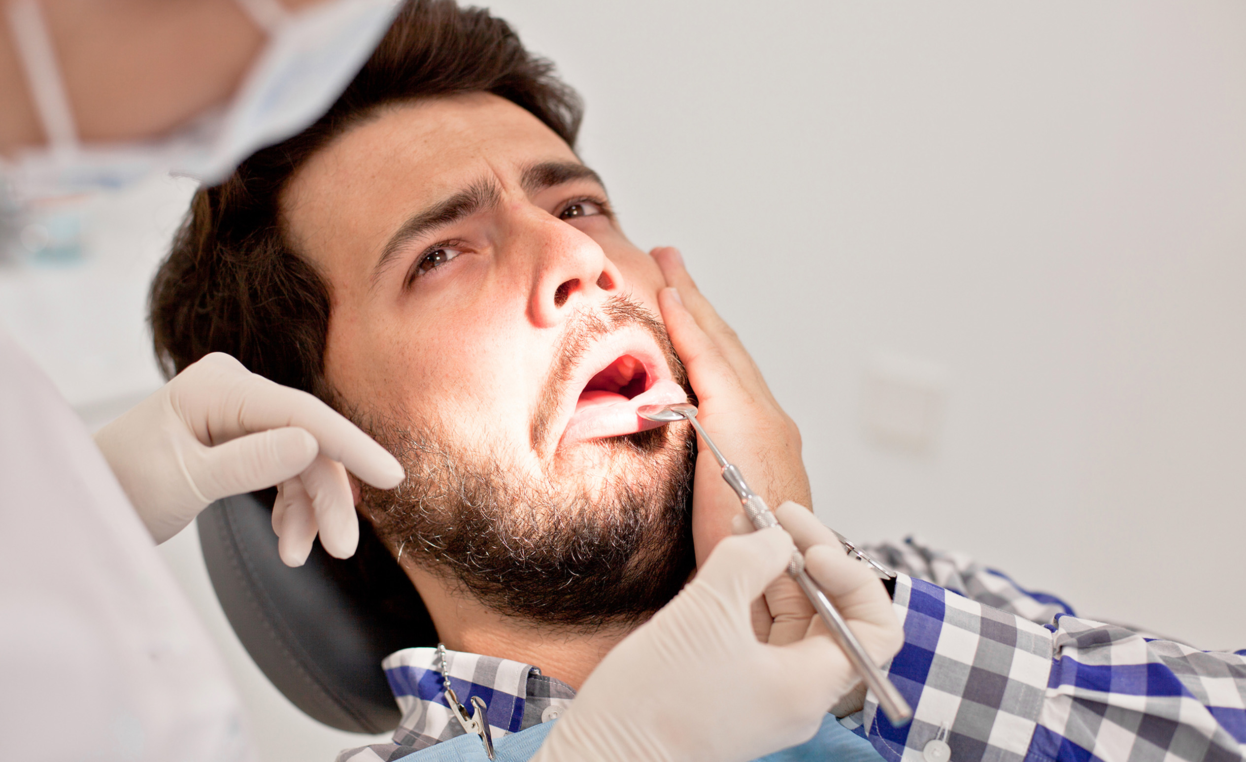 A dentist examines the teeth of this man because he got an insensible tooth.