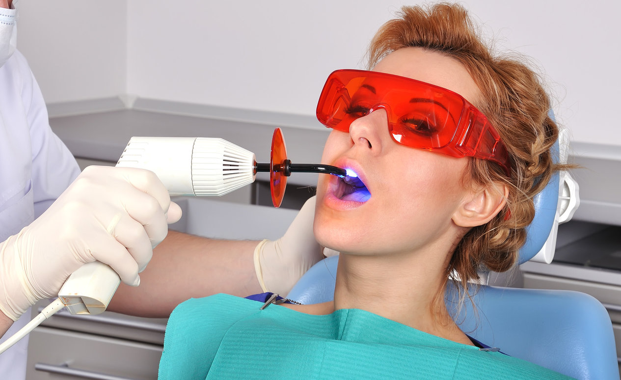 A red haired woman is sitting in the dentist's seat during a tooth filling.