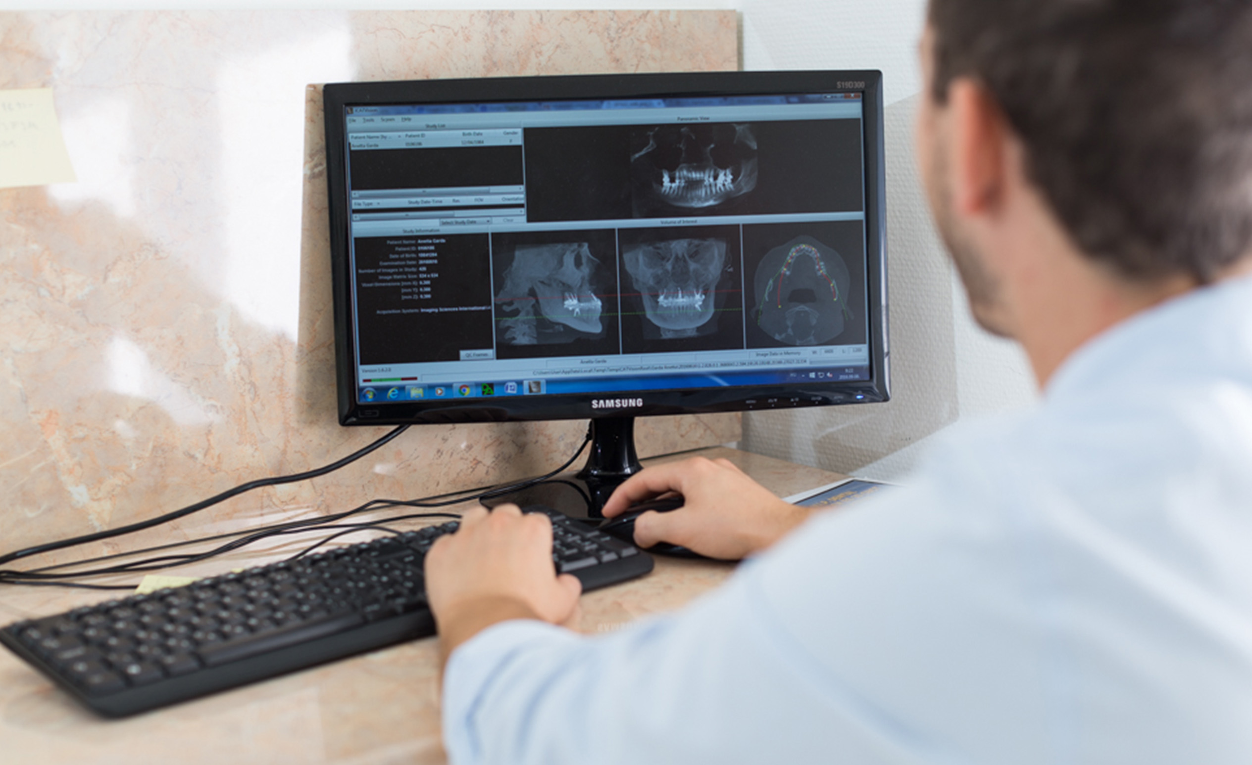 A Budapest dentist sitting at the computer works with a program which assists the inlay of a prothesis.