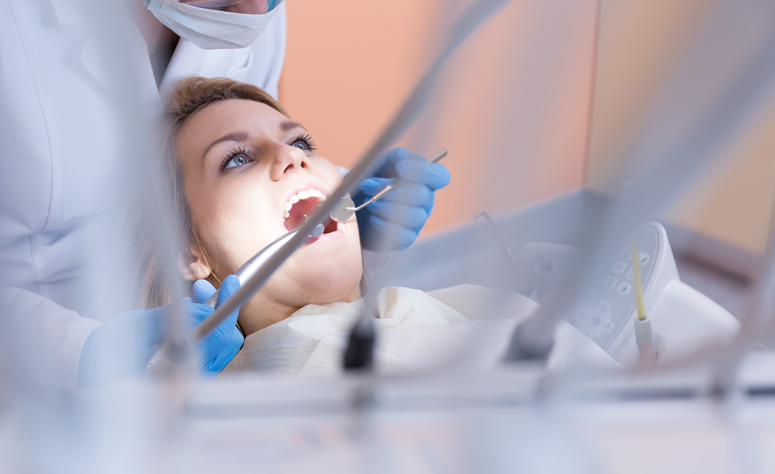 A blue-eyed woman is under a dental treatment (drilling a tooth) in a Budapest dentistry.