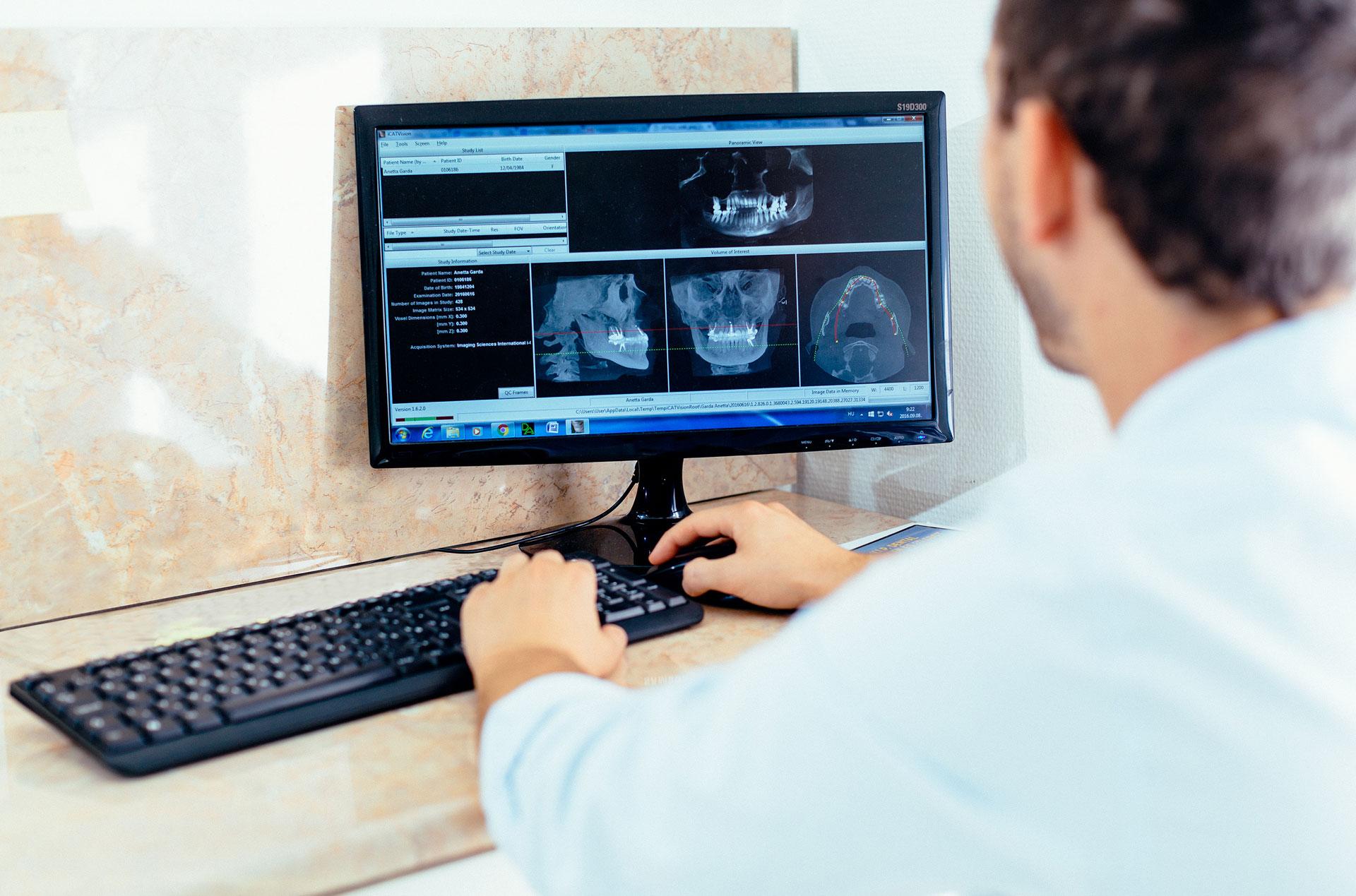Dr. Varajti Artúr fogorvos, szájsebész egy fogbeültetést támogató szoftvert használ a budapesti fogászati rendelőben.