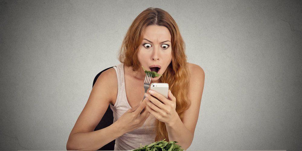 Vörös hajú nő eszik egy salátát, telefonon rossz híreket ad és döbbent arcot vág.