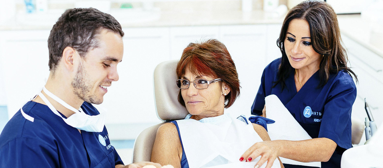 Fog implantátum beültetés előtt a fogorvos és a páciens beszélget. A páciens egy rögzített fogpótlást fog kapni.